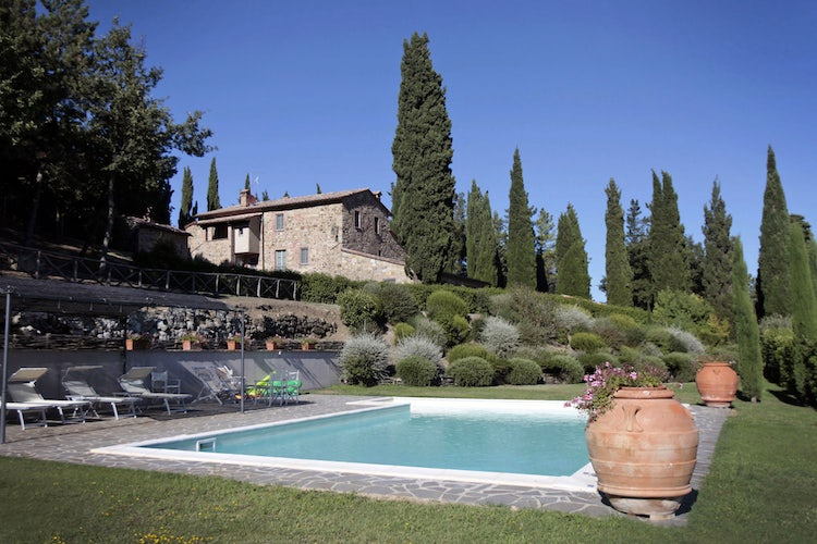 Spacious garden area with pool and lush green areas at Camporsevoli